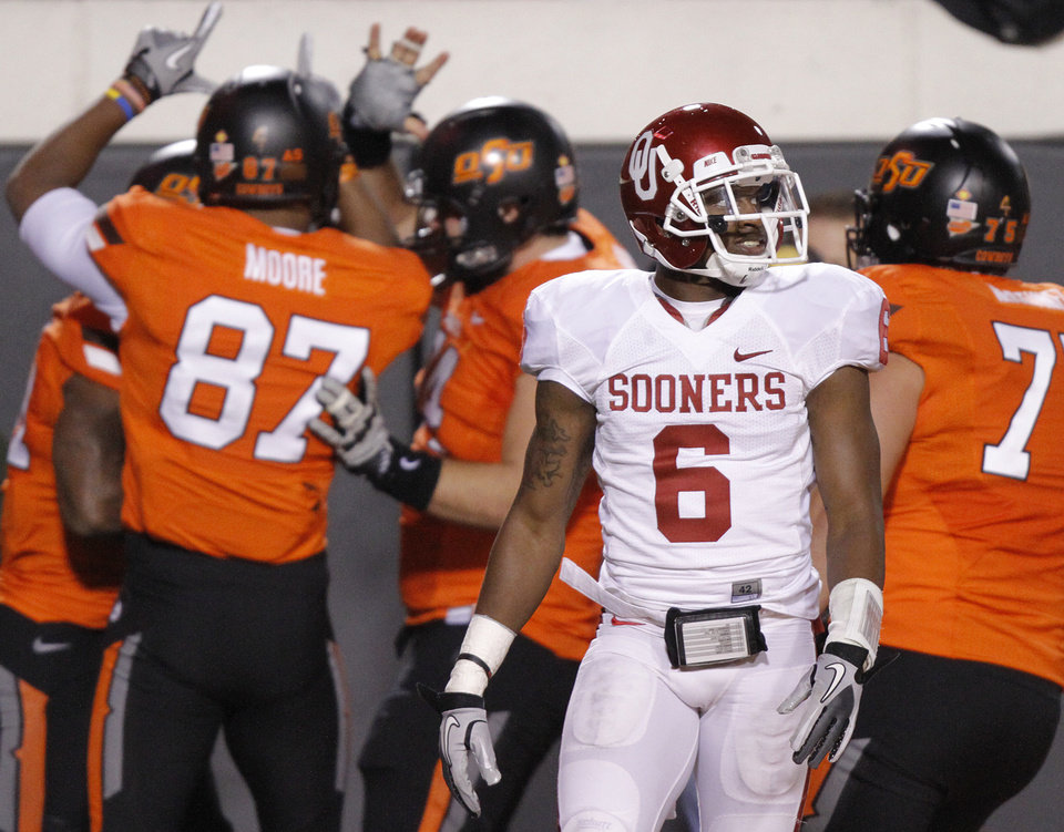 Photo - Oklahoma's Demontre Hurst (6) walks away as the Cowboys celebrate a touchdown during the Bedlam college football game between the Oklahoma State University Cowboys (OSU) and the University of Oklahoma Sooners (OU) at Boone Pickens Stadium in Stillwater, Okla., Saturday, Dec. 3, 2011. Photo by Chris Landsberger, The Oklahoman