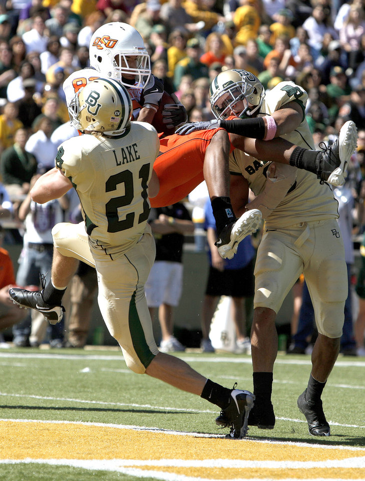 Photo - OSU's Dameron Fooks (83) socres a touchdown as Baylor's Jordan Lake (21) and during the college football game between Baylor University and Tim Atchison (8) bring him down Oklahoma State University (OSU) at Floyd Casey Stadium in Waco, Texas, Saturday, Oct. 24, 2009.  Photo by Sarah Phipps, The Oklahoman