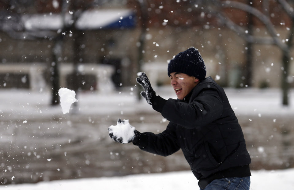 Photo - Chris Xiao throws a snowball at the University of Central Oklahoma in Edmond, Okla., Wednesday, Feb. 13, 2013.Photo by Sarah Phipps, The Oklahoman