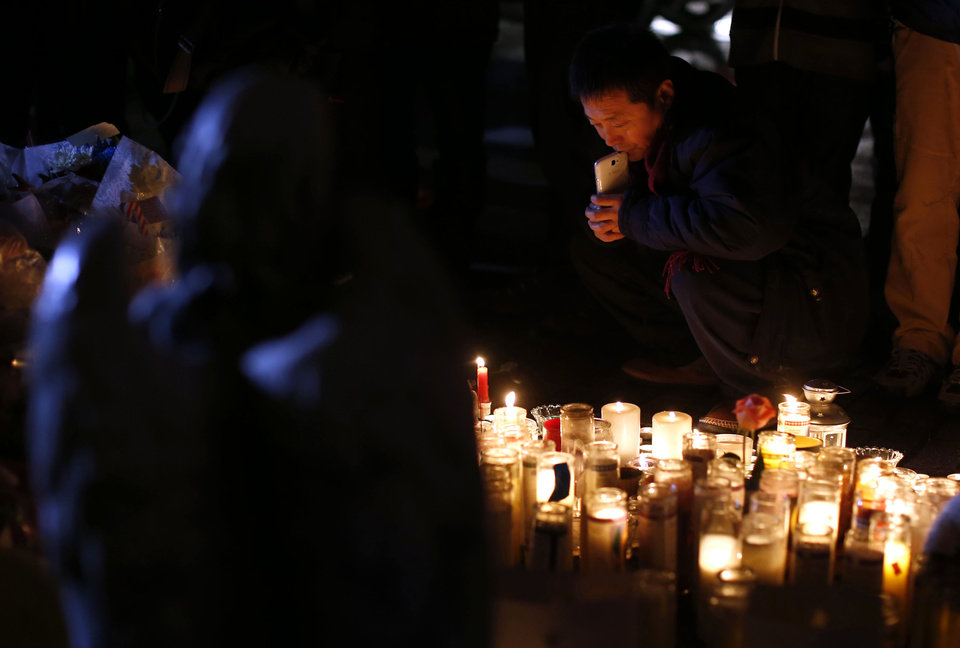Photo - An angel statue stands over a memorial to shooting victims as a man gazes at the candles placed there, Monday, Dec. 17, 2012, in Newtown, Conn.  A gunman walked into Sandy Hook Elementary School in Newtown Friday and opened fire, killing 26 people, including 20 children. (AP Photo/Jason DeCrow) ORG XMIT: CTJD119