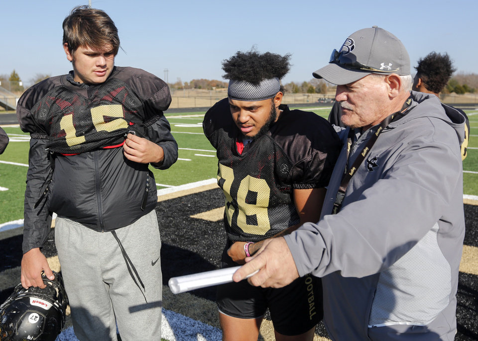 Photo -  Beggs coach David Tenison talks to quarterback Dalton Spring (15), left, and running back Jared Sutter (28) in the days following the death of senior running back Kayson Toliver. [Photo by Nate Billings, The Oklahoman]