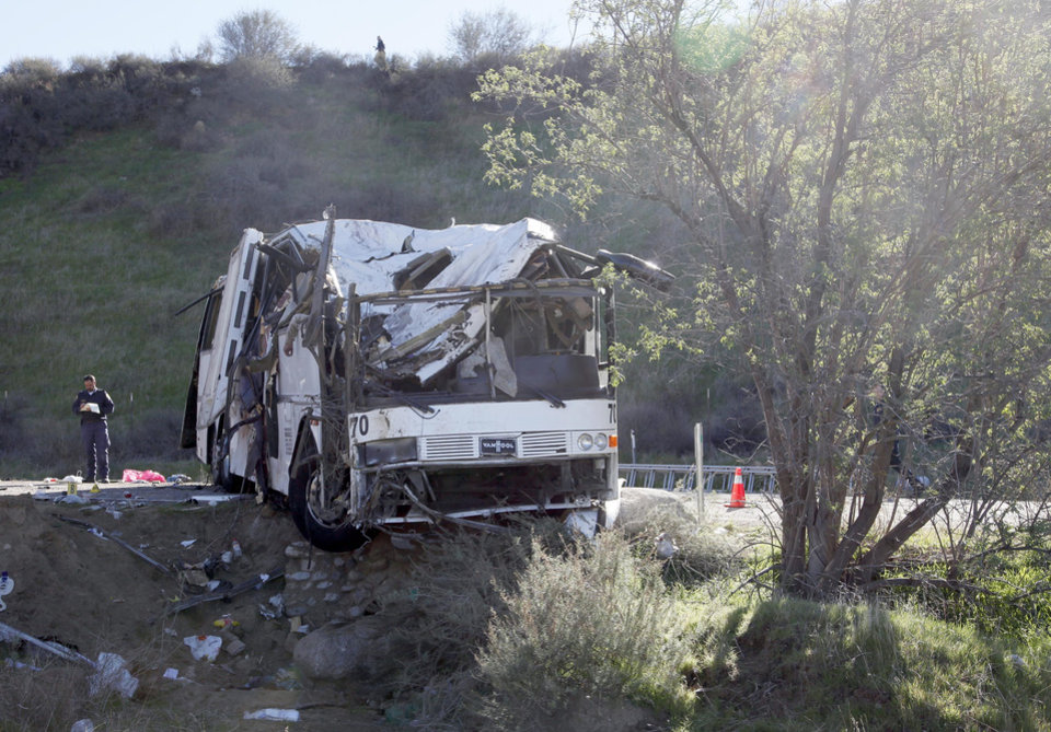Photo - An official takes notes Monday Feb. 4, 2013, at the scene of a tour bus crash near San Bernardino, Calif.  The tour bus carrying dozens of men, women and children from Tijuana, Mexico, crashed in the mountains of Southern California killing at least eight people, authorities said. ( AP Photo/Nick Ut)