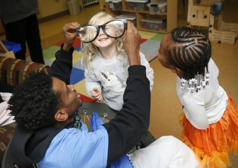 Photo -  Oklahoma City's Shai Gilgeous-Alexander puts a pair of oversize glasses on Bennett Schwarz, 4, while Camryn Davis, 5, watche. Thunder basketball players handed out candy and visited with children for Halloween at Special Care, 12201 N Western Ave., in Oklahoma City. [Nate Billings photos/The Oklahoman]
