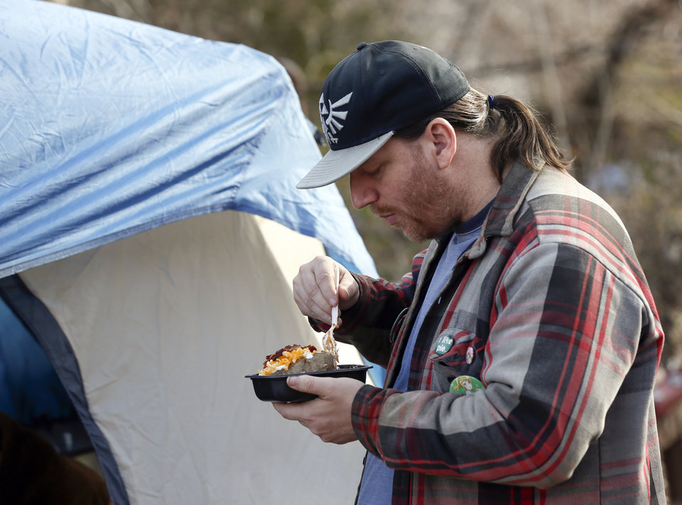 Photo - Joe Mertes, 39, eats lunch next to a tent where it was being served at 6100 S Cox, near the original location of Joe's Addiction, in Valley Brook, Okla., Monday, Dec. 23, 2019. While the new site for Joe's Addiction is not ready, Jamie Zumwalt, not pictured, and others continue to help the community of people in need who were being served by Joe's Addiction. [Nate Billings/The Oklahoman]