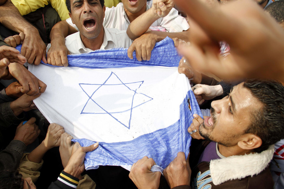 Egyptian protesters hold a representation of the Israeli flag and chant slogans during a protest in Cairo, Egypt, Friday, Nov. 16, 2012. In his Friday sermon at Al-Azhar, influential cleric Sheikh Yusuf al-Qaradawi, not shown, said the Islamic world would not be silent in the face of Israel's military operation in Gaza. (AP Photo/Mostafa Elshemy)