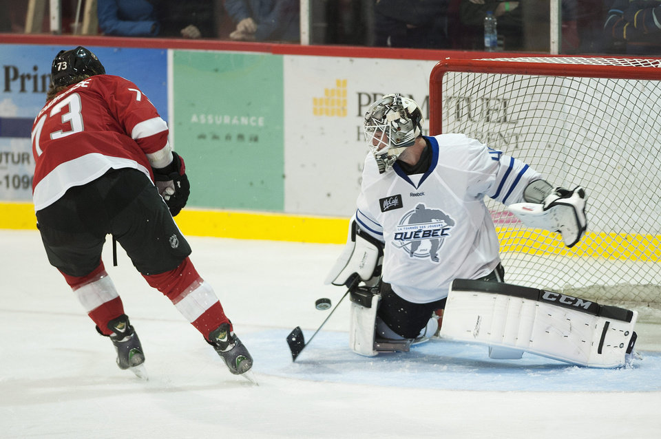 Photo -   Los Angeles Kings goaltender Jonathan Bernier makes a save against Ottawa Senators' Guillaume Latendresse during first period of a charity hockey game in Chateauguay, Quebec, Thursday, Sept. 27, 2012. (AP Photo/The Canadian Press, Graham Hughes)