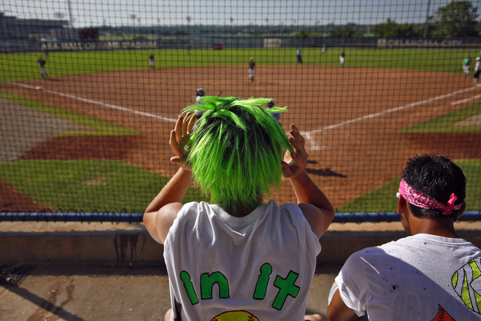 Photo - Rattan High School softball fan Derek Wolfe adjust his green wig while watching a game during the state championship softball tournament at ASA Hall of Fame Stadium on Wednesday, May 2, 2012, in Oklahoma City, Oklahoma. Photo by Chris Landsberger, The Oklahoman