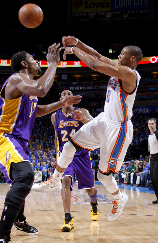Photo - Oklahoma City's Russell Westbrook (0) passes the ball around Los Angeles' Andrew Bynum (17), and Kobe Bryant (24) during Game 1 in the second round of the NBA playoffs between the Oklahoma City Thunder and L.A. Lakers at Chesapeake Energy Arena in Oklahoma City, Monday, May 14, 2012. Oklahoma City won 119-90. Photo by Bryan Terry, The Oklahoman