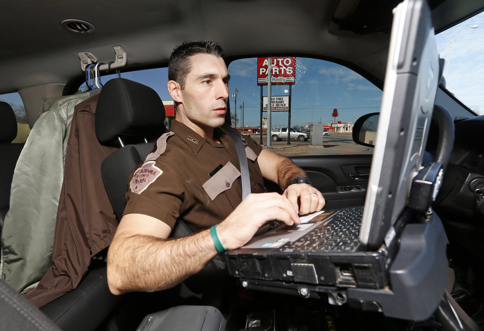 Photo -  Oklahoma Highway Patrol Trooper Brian Costanza checks his computer while on patrol in Okmulgee. Costanza was one of the officers who killed fugitive Michael Dale Vance Jr. during an Oct. 30 shootout. [Photo by Nate Billings, The Oklahoman]