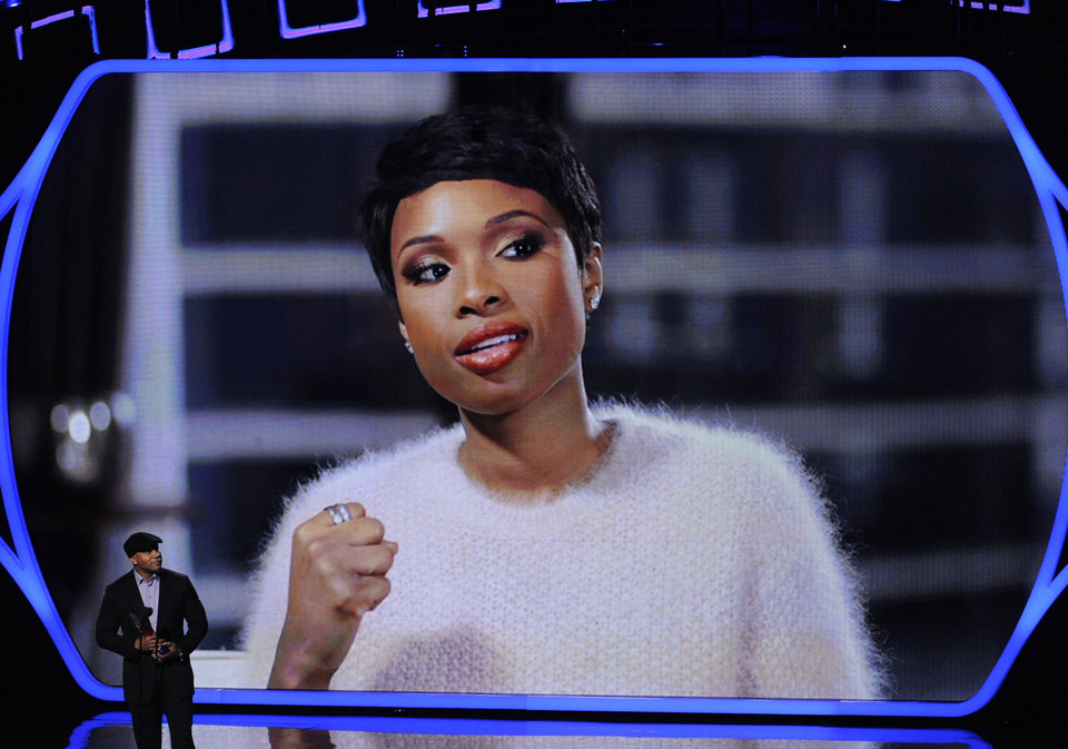 Photo - LL Cool J, left, presents the favorite humanitarian award to Jennifer Hudson, seen on screen, at the 40th annual People's Choice Awards at the Nokia Theatre L.A. Live on Wednesday, Jan. 8, 2014, in Los Angeles. (Photo by Chris Pizzello/Invision/AP)