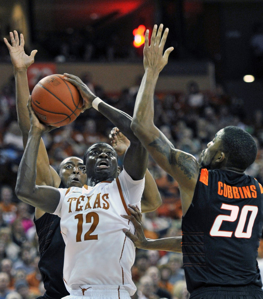 Photo - Texas guard Myck Kabongo (12) goes up for a shot against Oklahoma State guard Le'Bryan Nash, left, and Michael Cobbins (20) during the second half of an NCAA college basketball game Saturday, Jan. 7, 2012, in Austin, Texas. Kabongo led Texas with 15 points as Texas won 58-49. (AP Photo/Michael Thomas) ORG XMIT: TXMT108
