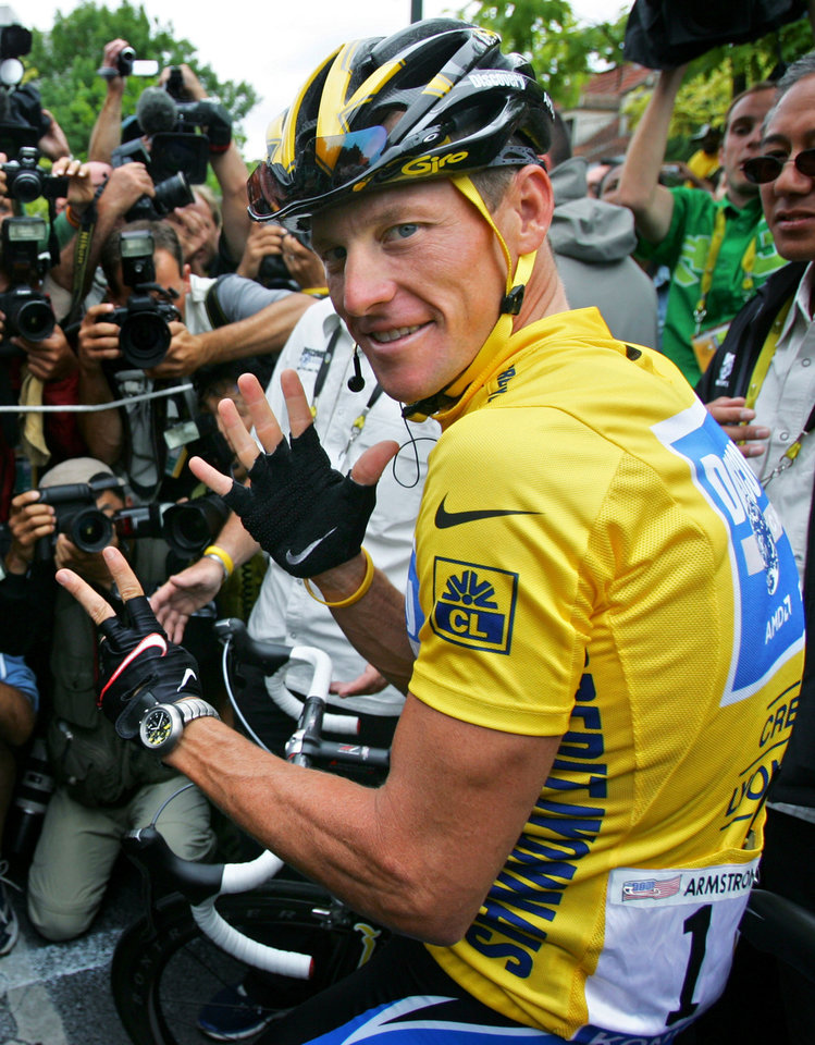 Photo - FILE - In this July 24, 2005, file photo, Lance Armstrong gestures for his seventh straight win in the Tour de France cycling race before the final stage between Corbeil-Essonnes, south of Paris, and the French capital. In 2005, Armstrong was also named Associated Press Male Athlete of the Year and ESPN's ESPY Award for Best Male Athlete. He later announced what would be a temporary retirement from cycling in 2005. (AP Photo/Peter Dejong, File)