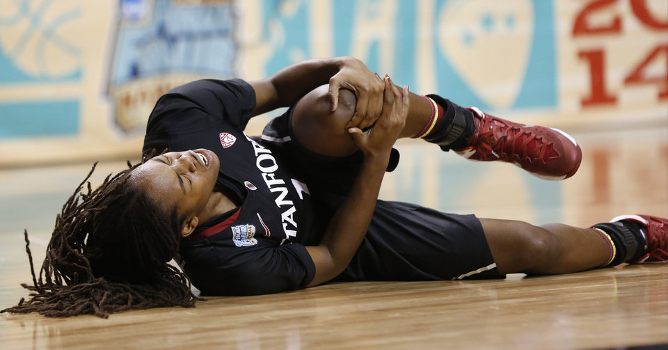 Photo - Stanford guard Lili Thompson (1) lies on the court after being injured against Connecticut during the second half of the semifinal game in the Final Four of the NCAA women's college basketball tournament, Sunday, April 6, 2014, in Nashville, Tenn. (AP Photo/John Bazemore)