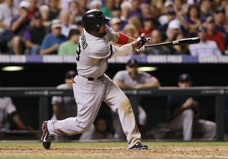 Photo - Boston Red Sox's Shane Victorino follows the flight of his three-run home run against the Colorado Rockies in the fourth inning of the Red Sox's 15-5 victory in a baseball game in Denver on Wednesday, Sept. 25, 2013. (AP Photo/David Zalubowski)