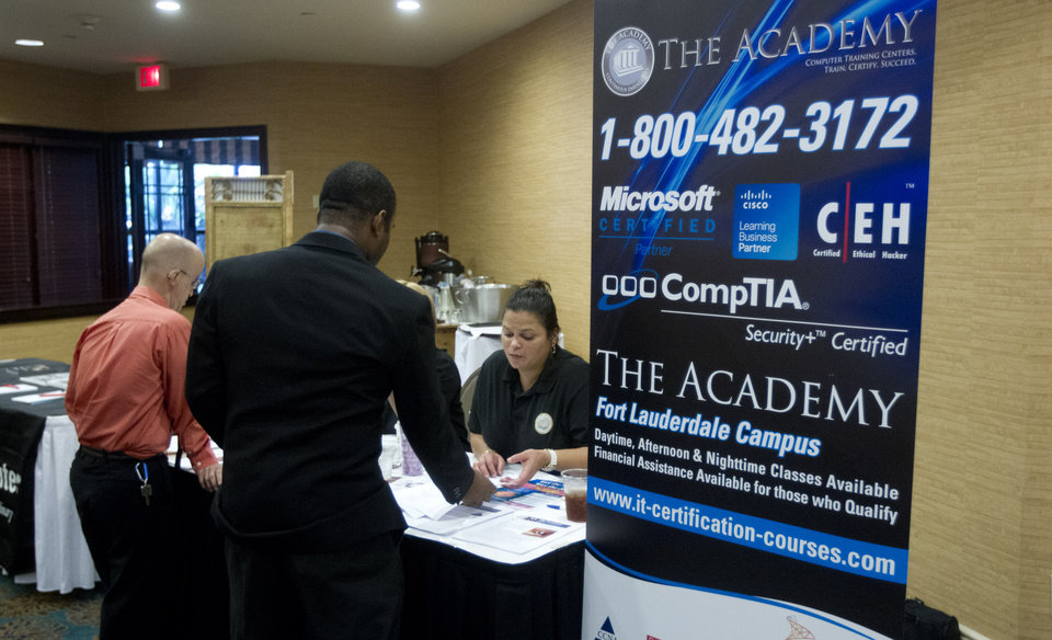 Photo - In this Friday, Nov. 30, 2012, photo, an unidentified job seeker talks to recruiters from a trade school at the Fort Lauderdale Career Fair, in Dania Beach, Fla. Weekly U.S. unemployment benefit applications fell 25,000 last week to a seasonally adjusted 370,000, the government said Thursday. The third straight drop shows a temporary spike caused by Superstorm Sandy has faded. (AP Photo/J Pat Carter)