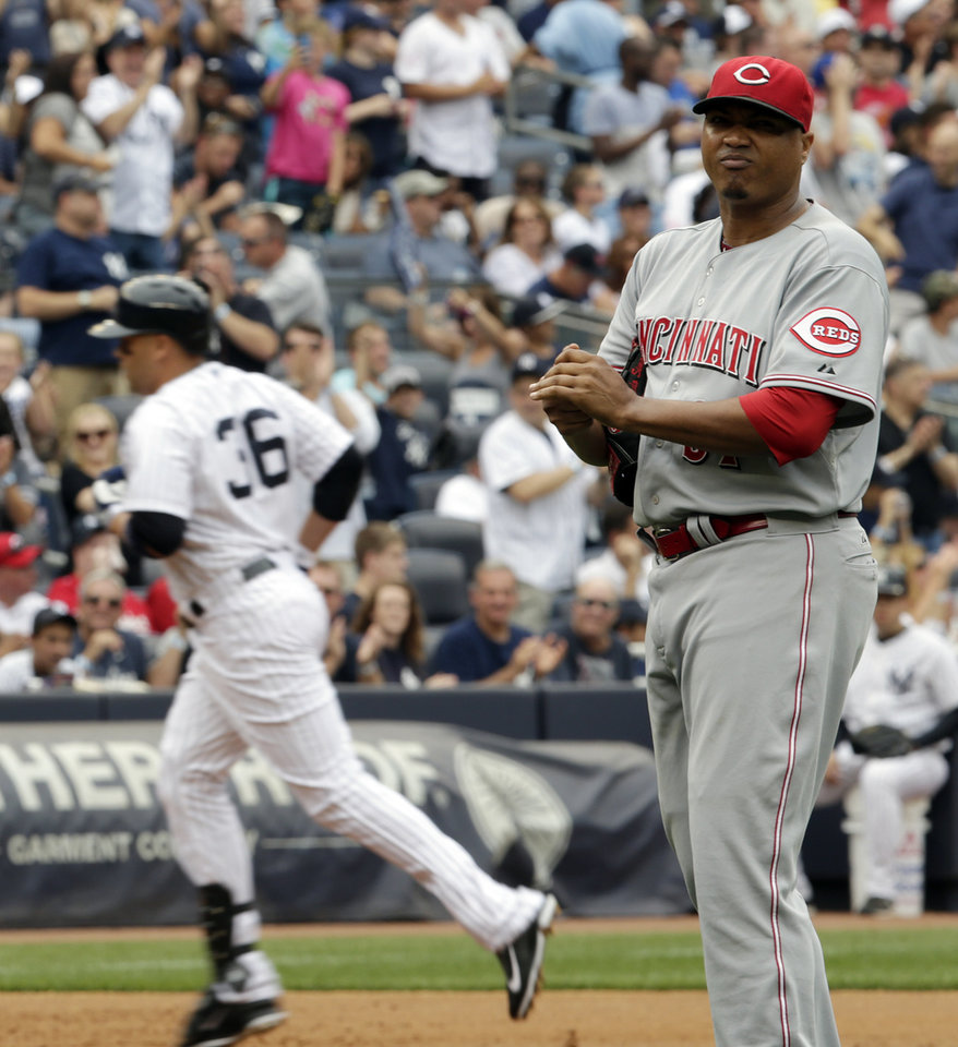 Photo - Cincinnati Reds starting pitcher Alfredo Simon, right, looks away as New York Yankees' Carlos Beltran runs the bases after hitting a home run off him during the second inning of a baseball game, Saturday, July 19, 2014, at Yankee Stadium in New York. (AP Photo/Julio Cortez)