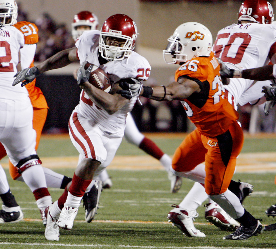 Photo - Oklahoma's Chris Brown (29) gets past Oklahoma State's Quinton Moore (26) during the second half of the college football game between the University of Oklahoma Sooners (OU) and Oklahoma State University Cowboys (OSU) at Boone Pickens Stadium on Saturday, Nov. 29, 2008, in Stillwater, Okla. STAFF PHOTO BY CHRIS LANDSBERGER