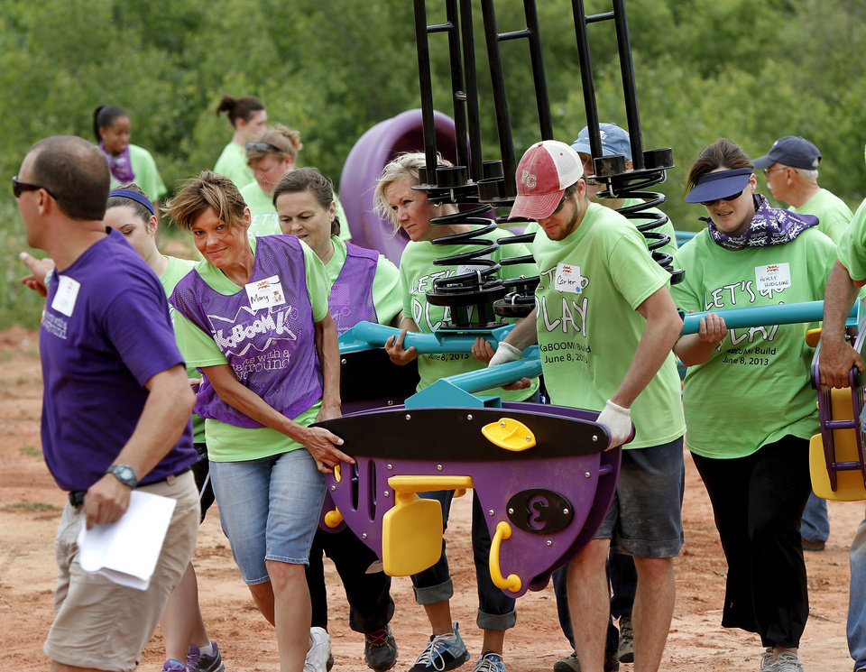It takes about eight people to carry this section of equipment to the playground to be installed. Organizers said about 140 volunteers from Partners in Public Health, Blue Cross and Blue Shield of Oklahoma, organizers from KaBOOM! and residents of the Oklahoma City community will provided the labor on Saturday, June 8, 2013, to build a new playground at the Northeast Regional Health and Wellness Center on NE 63 Street, east of MLK Blvd.  The new playground's design is based on drawings created by children who participated in a Design Day event in April.   Photo  by Jim Beckel, The Oklahoman.