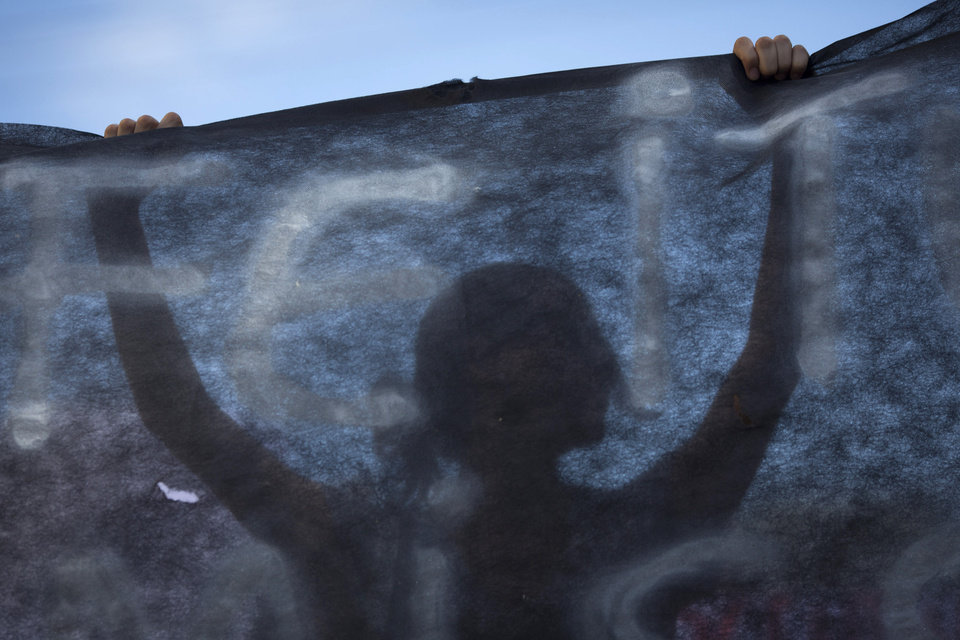 Photo - A woman holds up a black banner as people protest near the Kiss nightclub where a fire killed over 230 people in Santa Maria, Brazil, Tuesday, Jan. 29, 2013. The Rio Grande do Sul state forensics department raised the death toll Tuesday from 231 to 234 to account for three victims who did not appear on the original list of the dead. Authorities say more than 120 people remain hospitalized for smoke inhalation and burns, with dozens of them in critical condition, after the Sunday nightclub fire. (AP Photo/Felipe Dana)