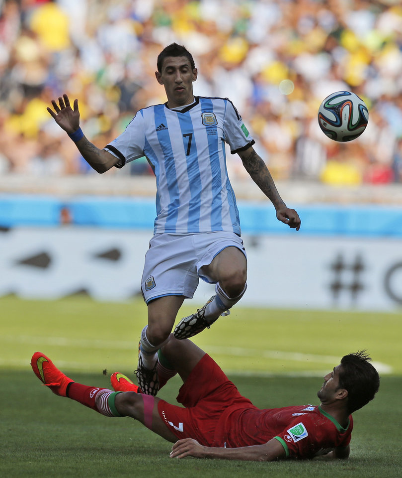 Photo - Iran's Masoud Shojaei, bottom, challenges Argentina's Angel di Maria during the group F World Cup soccer match between Argentina and Iran at the Mineirao Stadium in Belo Horizonte, Brazil, Saturday, June 21, 2014. (AP Photo/Victor R. Caivano)