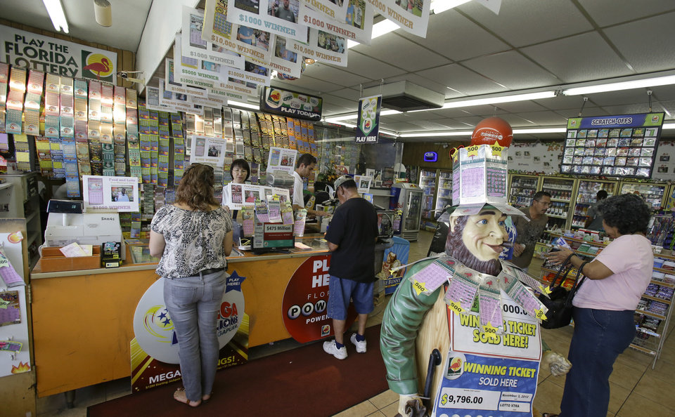 Photo - Customers purchase Powerball tickets seeking a payout of around $475 million at a convenience store, Thursday, May 16, 2013, in Orlando, Fla.  The prize is the third largest in lottery history, and the winning numbers will be drawn on Saturday. (AP Photo/John Raoux)