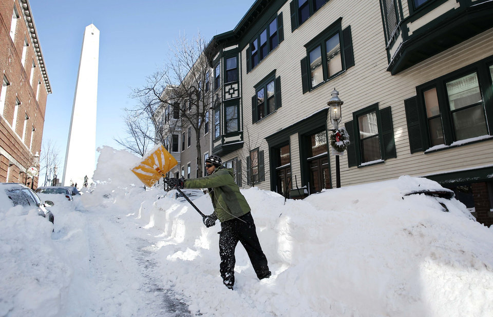 Photo - Jared Joiner shovels out his car in the shadow of the Bunker Hill monument in the Charlestown neighborhood of Boston Sunday, Feb.10, 2013. (AP Photo/Winslow Townson)