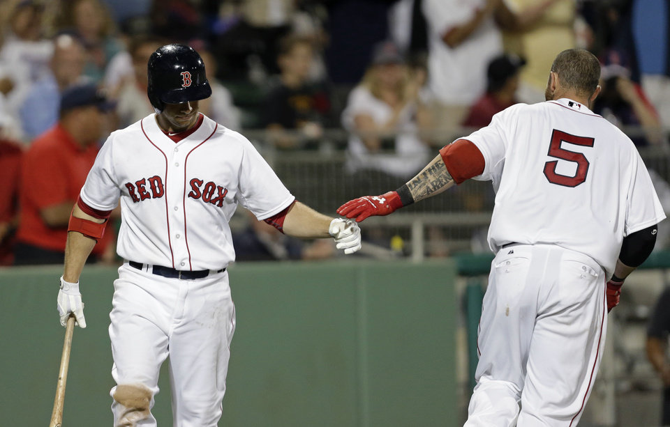 Photo - Boston Red Sox's Jonny Gomes (5) is greeted by Daniel Nava after hitting a solo homer in the seventh inning of an exhibition baseball game against the Philadelphia Phillies in Fort Myers, Fla., Saturday, March 15, 2014. (AP Photo/Gerald Herbert)