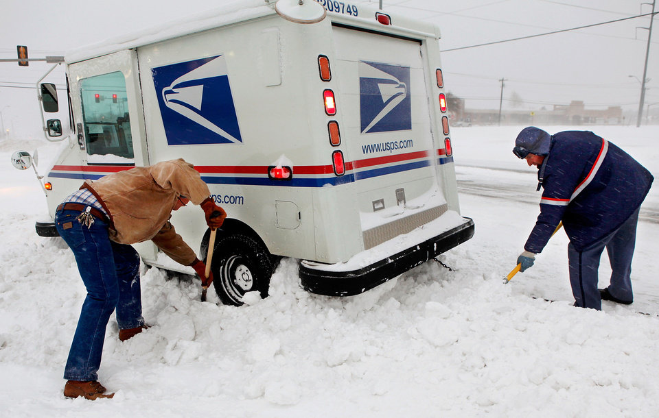 Russell Henderson noticed postal worker George Staros needed some help getting out of a snow drift on Douglas Blvd. near SE 15th Street. Henderson attached a chain from his truck to the mail truck and then helped dig snow from beneath the tires of Staros\' vehicle. Within ten minutes, the two men had freed the vehicle and Staros continued with his mail delivery duties. A winter storm created whiteout conditions and caused snow drifts that made problems for the few motorists who ventured out Tuesday morning, Feb. 1, 2011. Photo by Jim Beckel, The Oklahoman