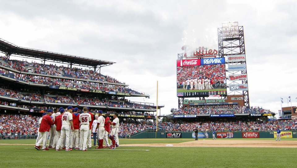 Photo - The Philadelphia Phillies come out to celebrate Jimmy Rollins becoming the all time hits leader for the Phillies during the fifth inning of a baseball game against the Chicago Cubs, Saturday, June 14, 2014, in Philadelphia.  (AP Photo/Chris Szagola)