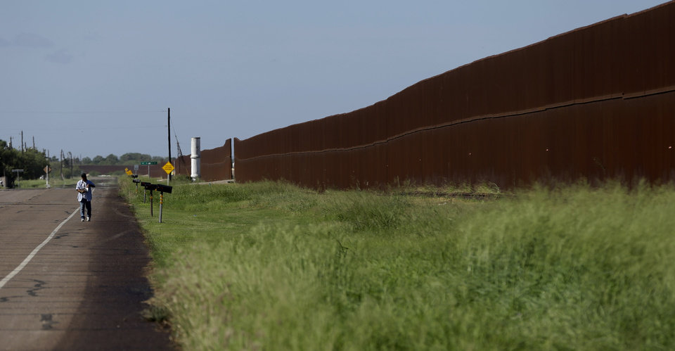 Photo -   In this Sept. 4, 2012, photo, a man retrieves his mail near the U.S.-Mexico border fence in Brownsville, Texas. Since 2008, hundreds of landowners on the border have sought fair prices for property that was condemned to make way for the fence, but many of them received initial offers that were far below market value. (AP Photo/Eric Gay)