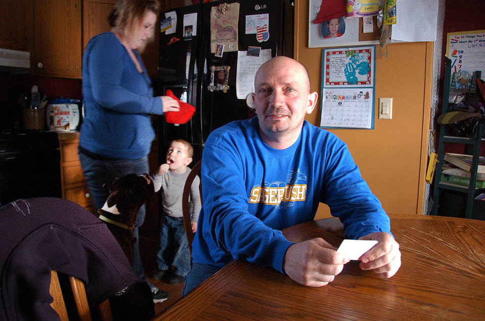 Photo - This Jan. 16, 2013 photo, Mike Cooley, one of 59 workers laid off from the Decker Coal mine along the Montana-Wyoming border, poses for a photo while discussing his future job prospects at his house in Sheridan, Wyo., with his wife and 2-year-old son, in the background. Hundreds of millions of tons of coal remain at Decker, in the heart of the nation's largest coal-producing region, but slackening demand prompted its owners to lay off almost half its workers this month. (AP Photo/Matthew Brown)