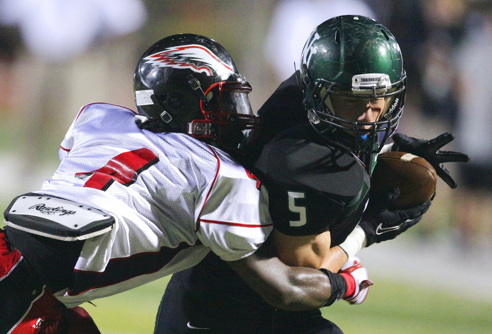 Photo - Timberwolf Beau Proctor (5) carries as he is pursued by Eagle Adrian Fletcher (4) as Del City plays Norman North in high school football at Harve Collins Field on Thursday, Sept. 9, 2010, in Norman, Okla.  Photo by Steve Sisney, The Oklahoman