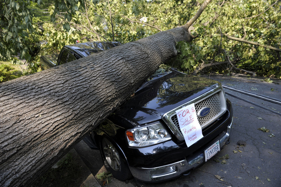 Photo -   Mike Wolfe's pick-up truck lies under a fallen tree in front of his house after a severe storm in Falls Church, Va., Saturday, June 30, 2012. Wolfe's daughter Samanth Wolfe created the for sale sign as a joke. (AP Photo/Cliff Owen)