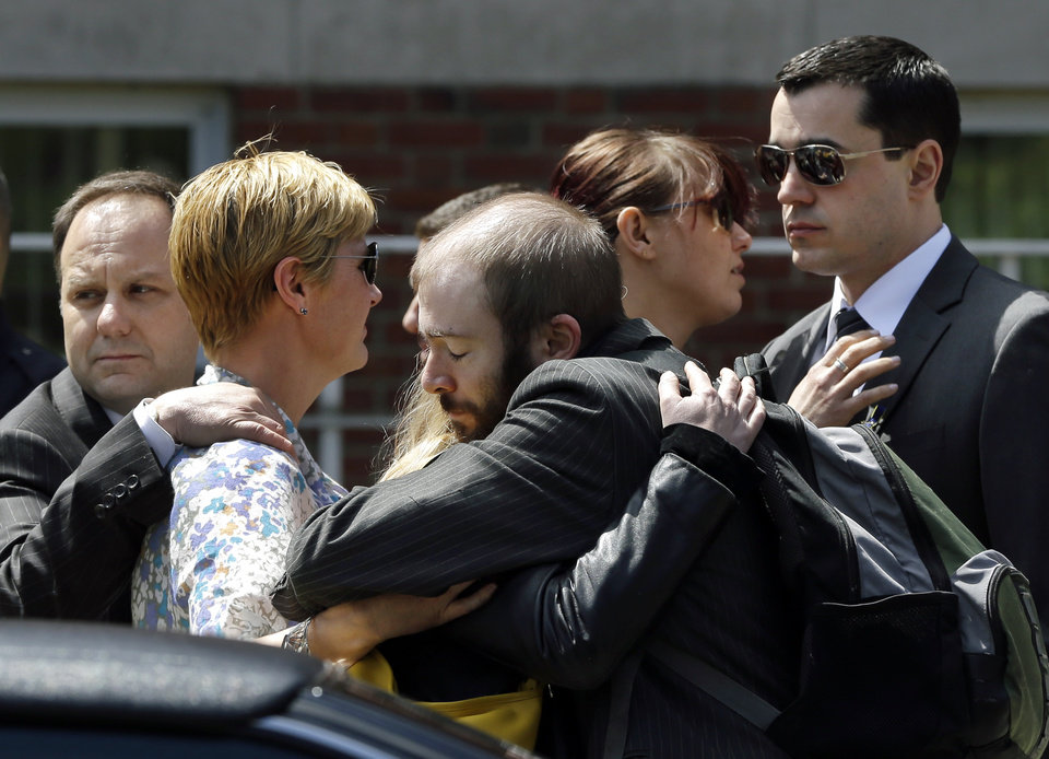Photo - Mourners hug as they leave the funeral for Boston Marathon bomb victim Krystle Campbell, 29, at St. Joseph's Church in Medford, Mass. Monday, April 22, 2013. Hundreds of family and friends packed the church in Medford, Mass., for Campbell's funeral, while dozens more waited outside after being turned away. (AP Photo/Elise Amendola)