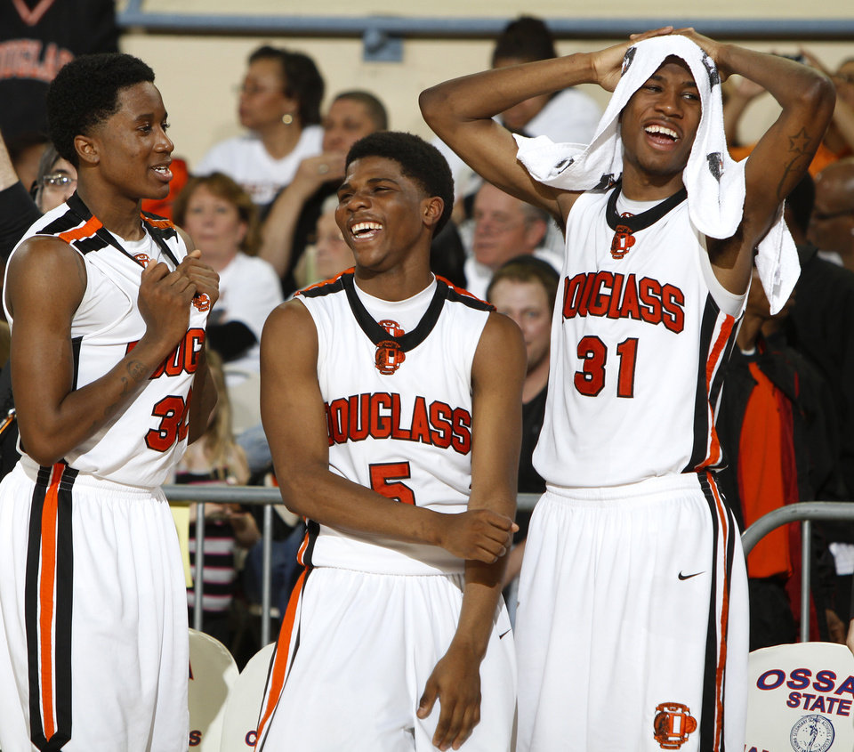 Photo - Najee Cox, left, Stephen Clark, and Dydrell Post of Douglass celebrate in the final minutes of their 86-53 win over Anadarko in the Class 4A boys high school state basketball championship game at State Fair Arena in Oklahoma City, Saturday, March 10, 2012. Photo by Bryan Terry, The Oklahoman
