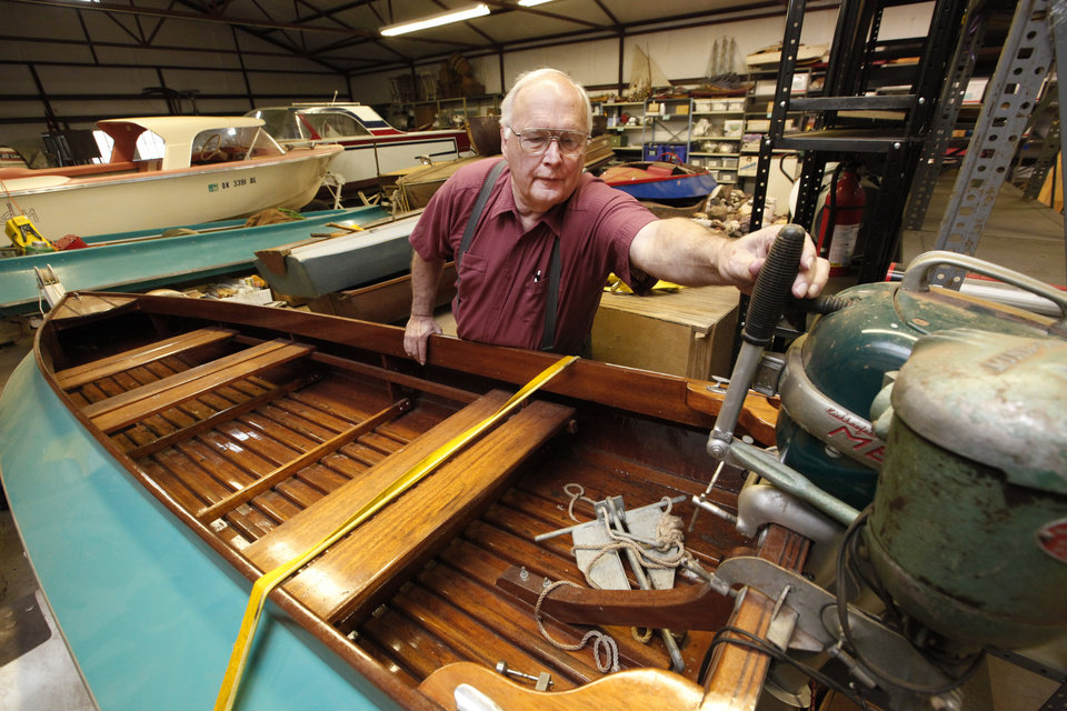 Photo - Karl White with a 1952 Skeeter bass fishing boat, part of his $5 million fishing collection.  Photo By David McDaniel, The Oklahoman