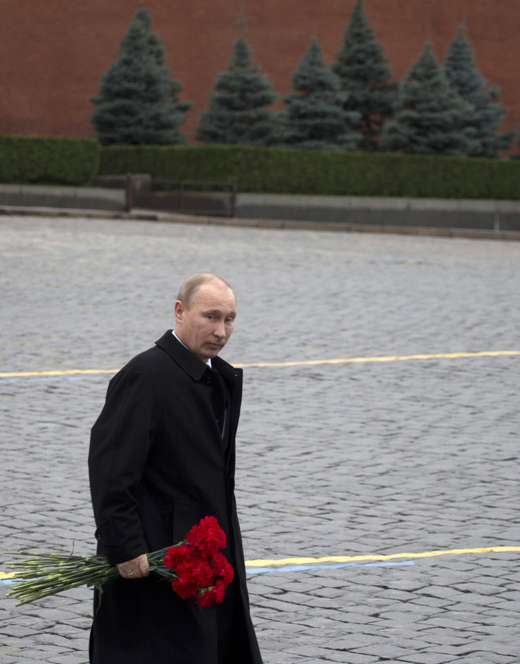 Russian President Vladimir Putin walks with flowers at the Red Square to place them at a statue of Minin and Pozharsky, the leaders of a struggle against foreign invaders in 1612, to mark the National Unity Day, Sunday, Nov. 4, 2012. The new holiday was created in 2005 to replace the traditional Nov. 7 celebration of the 1917 Bolshevik rise to power. The Kremlin has tried to give it historical significance by tying it to the 1612 expulsion of Polish and Cossack troops who briefly seized Moscow at a time of political disarray. (AP Photo/ Misha Japaridze)