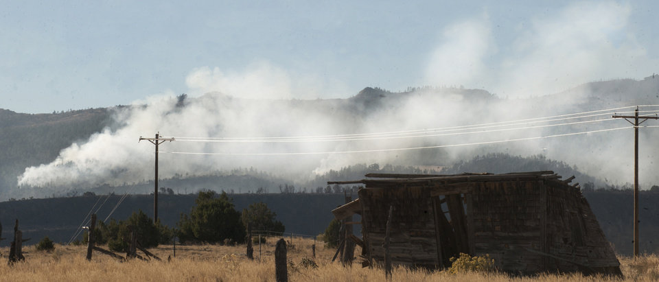 Photo -   Smoke rises behind one of the buildings of the historic stage coach stop at the top of Jackson Hill just east of Wetmore, Colo., Wednesday morning, Oct 24, 2012. Winds subsided early in the morning and the smoke from the western end of the fire subsided a little but the eastern end in western Pueblo County was still producing lots of smoke. (AP Photo/Pueblo Chieftain, Chris McLean)