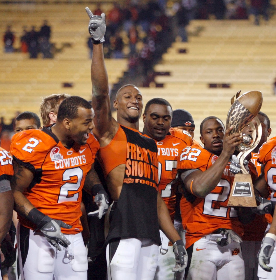 Photo - The OSU Cowboys, including from left, Rodrick Johnson (2), Adarius Bowman (12), Marque Fountain (97), and Dantrell Savage (22) celebrate with the Insight Bowl Trophy after the Insight Bowl college football game between Oklahoma State University (OSU) and the Indiana University Hoosiers (IU) at Sun Devil Stadium on Monday, Dec. 31, 2007, in Tempe, Ariz. OSU won, 49-33. BY NATE BILLINGS, THE OKLAHOMAN