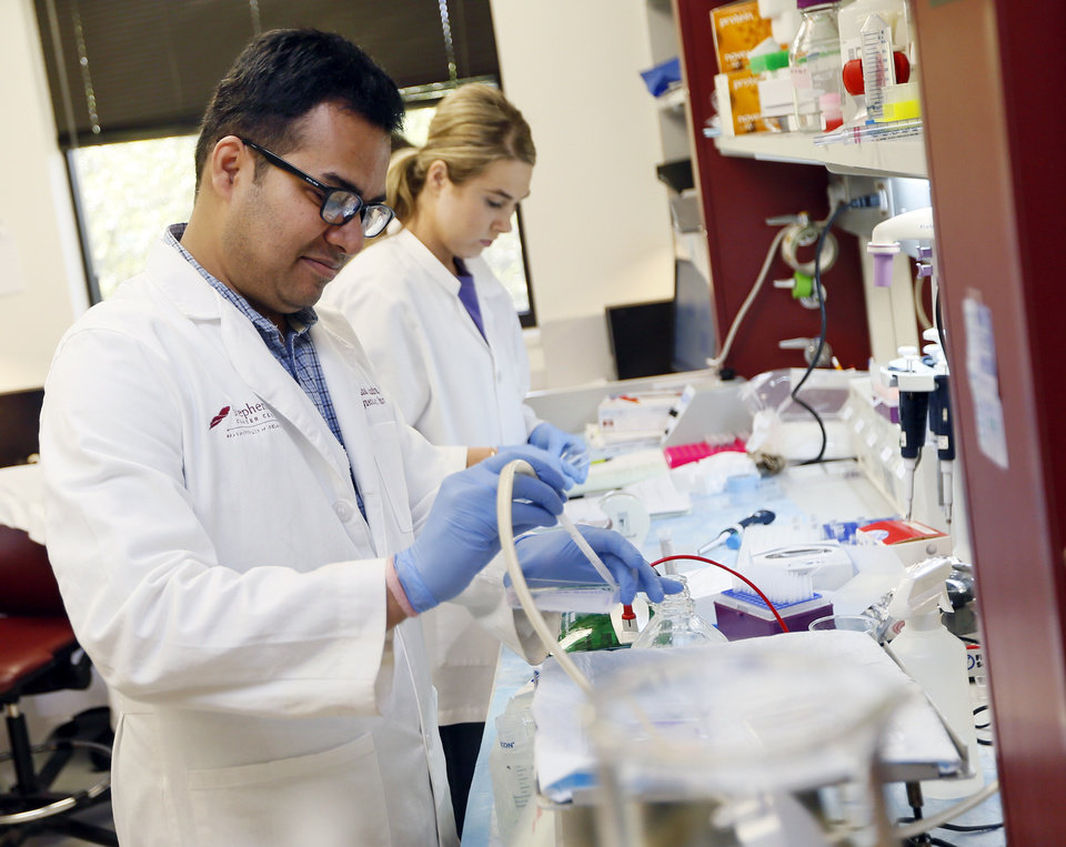 Photo - Vishal Chandra, postdoctoral fellow, left, and Cassadie Holybee, an undergraduate from Cameron University, work on a cervical cancer drug in the laboratory of Dr. Doris Mangiaracina Benbrook, Stephenson Cancer Center researcher, not pictured, in the Stanton L. Young Biomedical Research Center in Oklahoma City, Wednesday, June 22, 2016. Photo by Nate Billings, The Oklahoman
