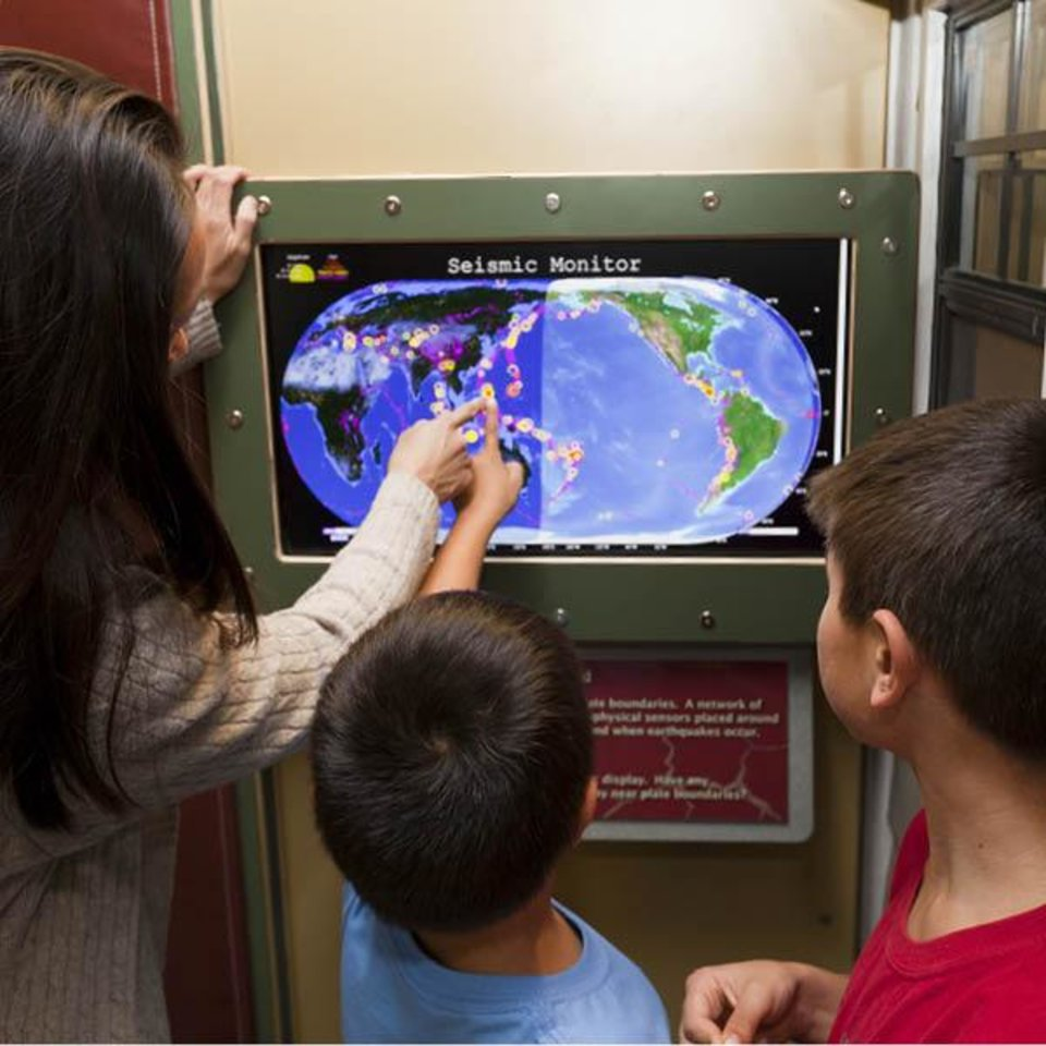 Photo -  Children watch how continents move and re-form on a touch-screen map that is part of the traveling exhibit,