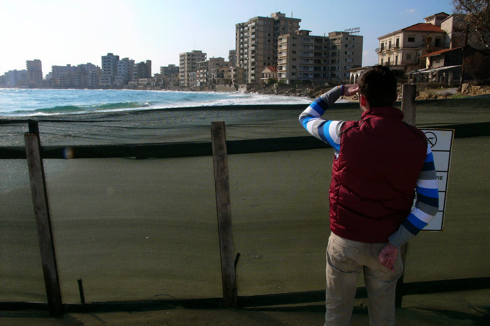 Photo - A man looks at deserted hotels in an area used by the Turkish military, in the Turkish occupied area, in abandoned coastal city of Varosha in Famagusta, southeast Cyprus, Friday, Jan. 17, 2014. The town's crumbling, war-scarred beachfront hotels have become an emblem of the country's division between Turks and Greeks. In 40 years, few have set foot inside the town, which remains heavily guarded by the Turkish army and twists of barbed wire. But that grim scene could present a rare opportunity. Massachusetts Institute of Technology architecture professor Jan Wampler calls it the greatest challenge of his career: he and a team of architects, urban planners, business leaders and peace activists hope to rebuild an entire town to correct past errors and mold a sustainable, ecological habitat. (AP Photo/Petros Karadjias)