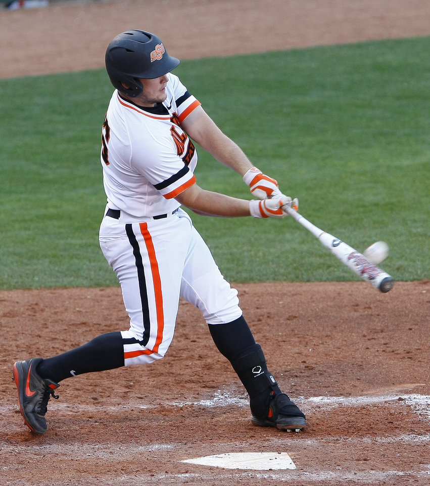 Photo - Oklahoma State's Zach Fish hits a grand slam in the bottom of the sixth inning of a first-round game against Oklahoma in the Big 12 conference NCAA college baseball tournament in Oklahoma City, Wednesday, May 21, 2014. (AP Photo/Alonzo Adams)