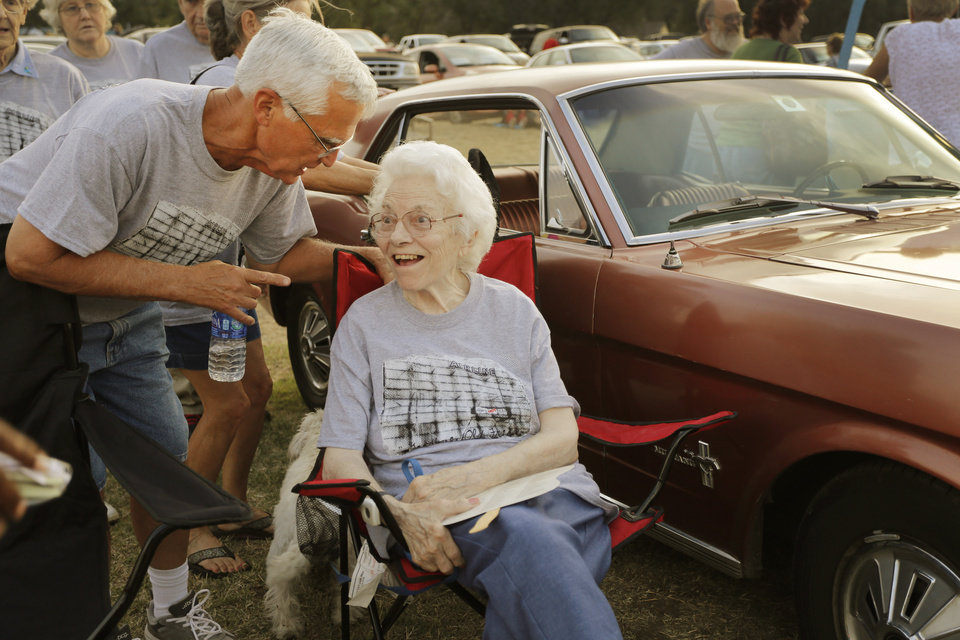 Photo - Charles Hall, whose family managed the drive in talks with Geneva Alston, who, with her husband ran the drive in at the Airline Drive-in movie theater in Ponca City Thursday, August 14, 2014. Parked next to them is Geneva's 1966Ford Mustang that she and her husband drove to work every day. Photo by Doug Hoke, The Oklahoman