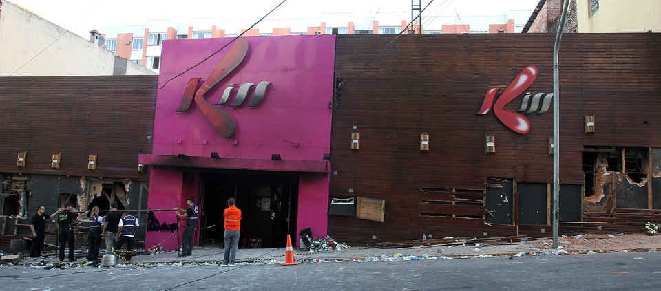 Photo - Police investigators inspect the entrance of the Kiss nightclub in Santa Maria city, Rio Grande do Sul state, Brazil, Sunday, Jan. 27, 2013. Flames raced through the crowded nightclub in southern Brazil early Sunday, killing more than 230 people as panicked partygoers gasped for breath in the smoke-filled air, stampeding toward a single exit partially blocked by those already dead. (AP Photo/Nabor Goulart)