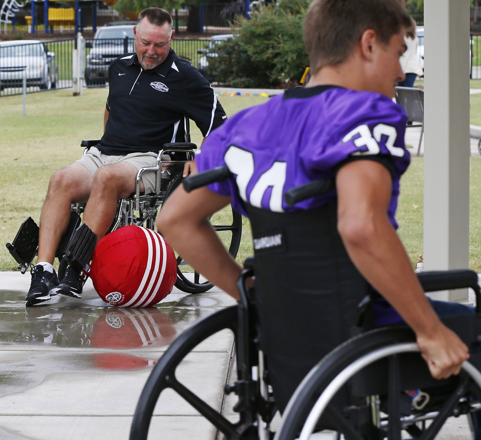 Bethany assistant coach Jerry Griffin, left, tries to direct an inflatable ball from a wheelchair while competing against player Carson Woods in an obstacle course designed to show them what it is like to have some of conditions of patients at The Children's Center in Bethany, Okla., Thursday, Sept. 27, 2012. The Bethany football team visited the center as part of the lead up to The Children's Center Bowl. Photo by Nate Billings, The Oklahoman