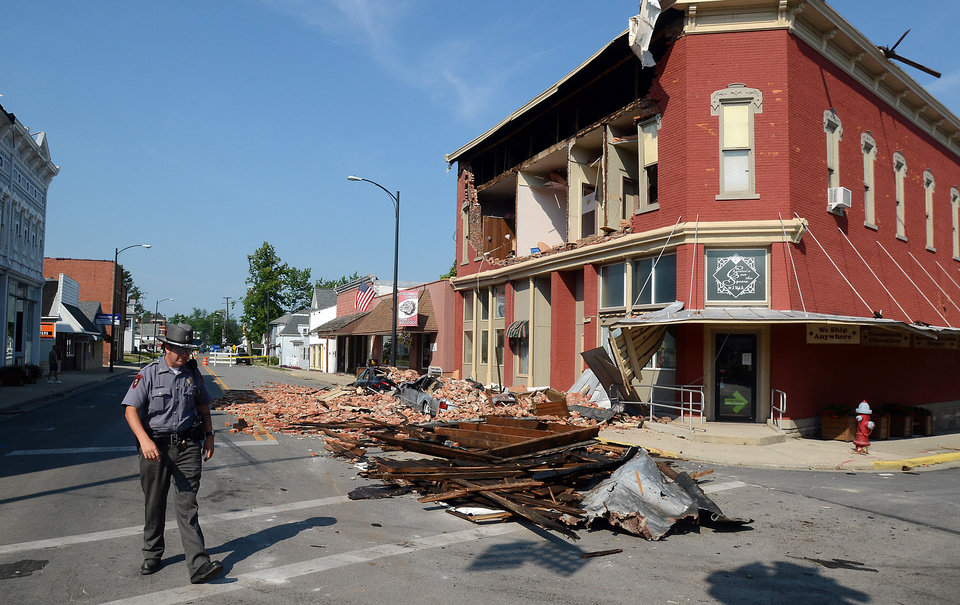 Photo -   Police chief, Nick Gilgenbauch walks past a brick wall Monday, July 2, 2012, which fell Friday from the second story of the Christie's on the Square store in Columbus Grove, Ohio, and crushed, two vehicles parked in front. A structural engineer is in Columbus Grove, Ohio on Monday to survey damage. (AP Photo/The Lima News, Craig J. Orosz) MANDATORY CREDIT