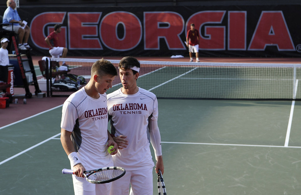 Photo - Oklahoma's Andrew Harris, left, and playing partner Guillermo Alcorta strategize against USC opponents Connor Farren and Roberto Quiroz during a men's team doubles match in the NCAA Division I tennis championships, Tuesday, May 20, 2014, in Athens, Ga. (AP Photo/David Tulis)