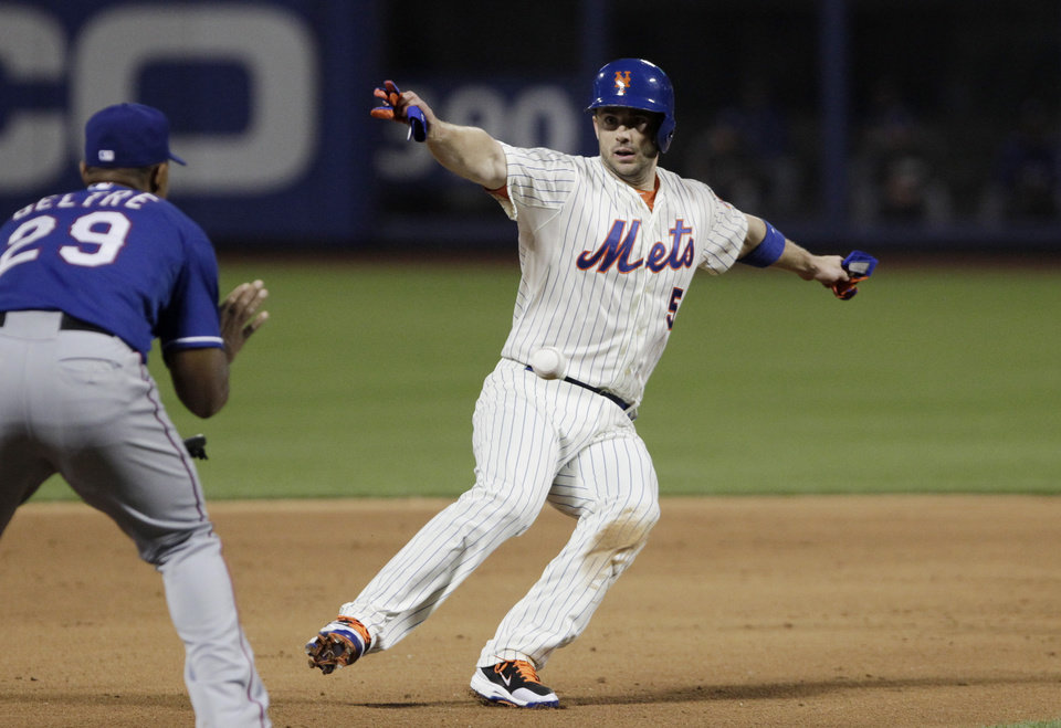 Photo - New York Mets David Wright is caught between second and third base in a run down by Texas Rangers third baseman Adrian Beltre in the fifth inning of a baseball game at Citi Field, Saturday, July 5, 2014 in New York. (AP Photo/Mark Lennihan)