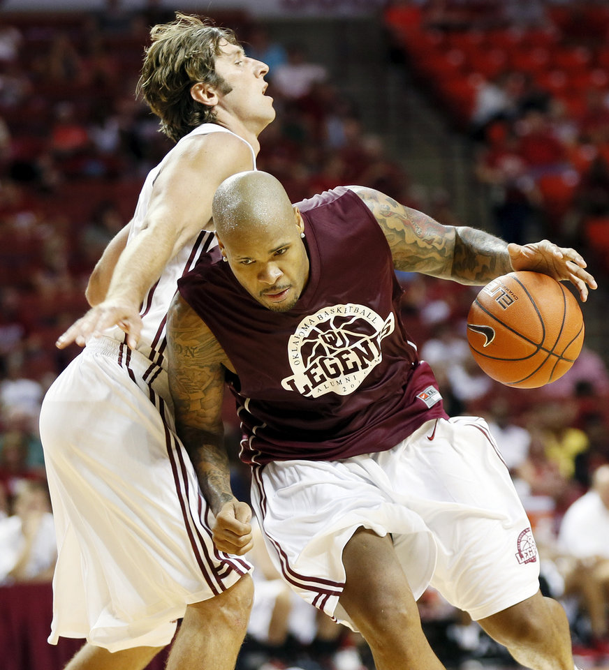 Photo - Aaron McGhee, right, drives against Jozsef Szendrei during the OU Legends Alumni Game in Lloyd Noble Center in Norman, Okla., Saturday, Aug. 23, 2014. The game is part of the Sooner Basketball Family Weekend. Photo by Nate Billings, The Oklahoman